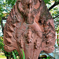 Garuda Sculpture in Siem Reap, Cambodia<br /> The bas-relief in the center of this fan-like sculpture is Garuda. This Buddhist, mythological deva (or tep in Khmer) has the crowned head of a predatory bird (similar to an eagle) and a human body with extraordinary strength and power. According to legend, their golden wingspan stretched for miles. The parents for this &ldquo;king of the birds&rdquo; were Kashyap and Vinata. Also called a Suparna, this supernatural deity is the mortal enemy of the nāga (half snake and half human). They were born by his stepmother, Kadru.