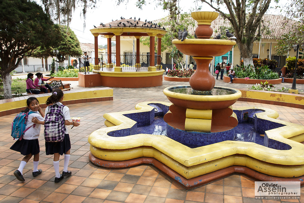 Two girls go past a park fountain as they walk back from school in the town of Valle de Angeles, Honduras on Friday April 26, 2013.