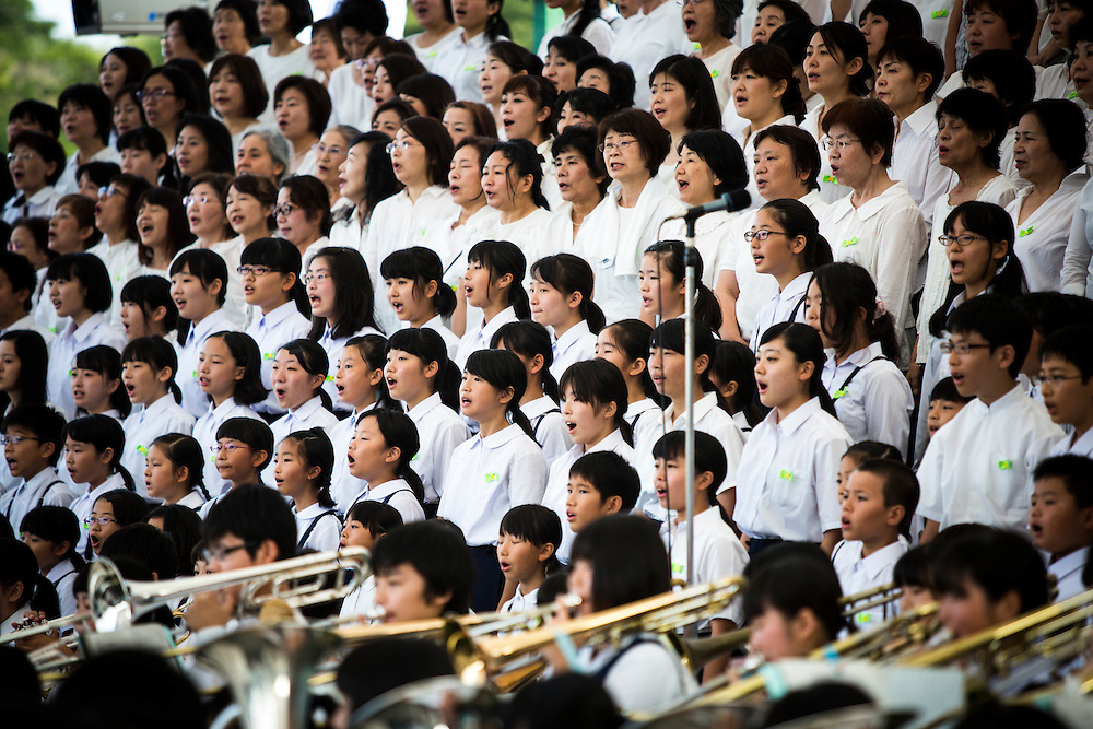 "HIROSHIMA, JAPAN - AUGUST 6 : Youth chorus singing the ""Hiroshima Peace Song"" during the 71st anniversary of the atomic bombing on Hiroshima at Hiroshima Peace Memorial Park in Hiroshima, western Japan, Saturday, August 6, 2016. Japan marked the 71st anniversary of the atomic bombing on Hiroshima. On August 6, 1945, during World War II, the United States dropped a uranium gun-type atomic bomb named ""Little Boy"" on the city of Hiroshima which instantly killed an estimated 80,000 people, tens of thousands more would later die of radiation exposure. Three days later, a second American B-29 bomber dropped a plutonium implosion-type bomb ""Fat Man"" on Nagasaki, killing an estimated 40,000 people.  (Photo: Richard Atrero de Guzman/NURPhoto)"
