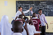 VSO volunteer Paul Jennings and local teacher Rebecca Ngovano high five at then end of a successful training session. Paul has been working with Rebecca for over 6 months to improve teaching methodologies in classrooms. Angaza school, Lindi, Tanzania