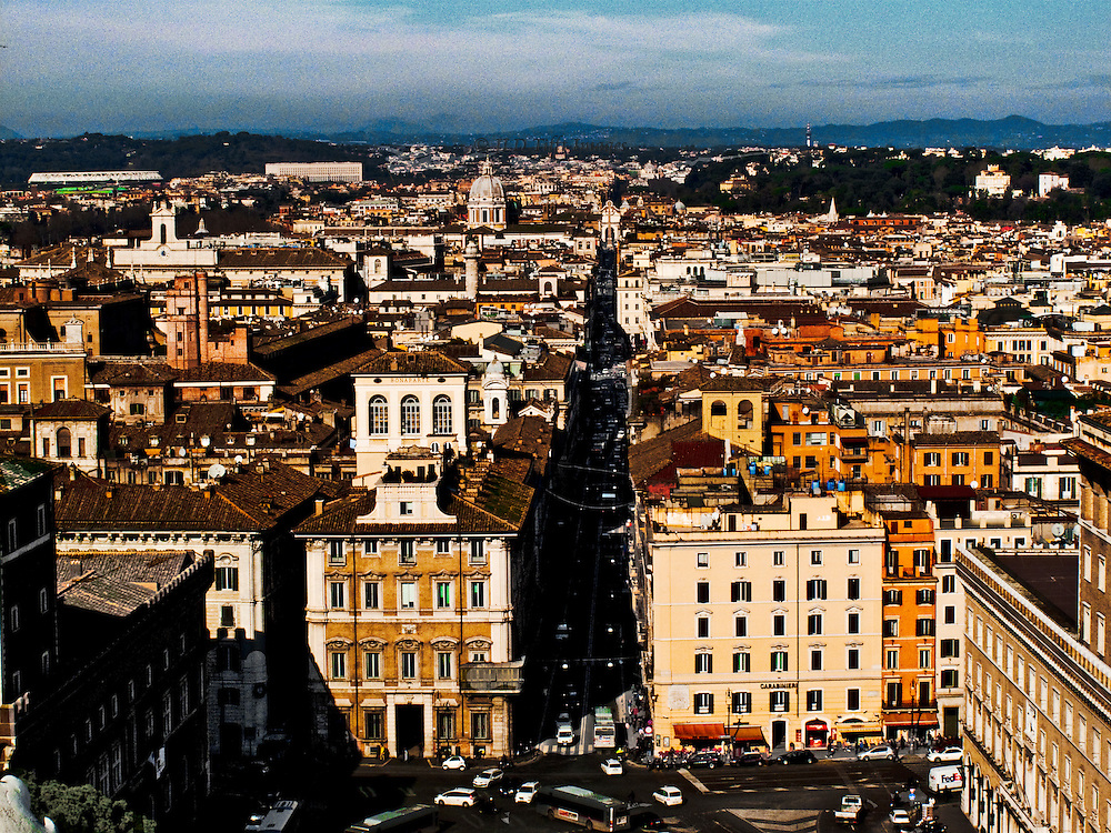View from Piazza Venezia along Il Corso toward the Piazza del Popolo, seen from above, on the roof of the Vittorio Emmanuele monument .  City rooftops and the rolling landscape beyond to the blue horizon.  Late afternoon slanted sunlight and heavy shadow along the street.