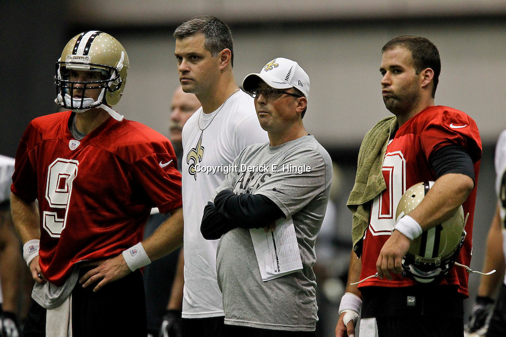 July 27, 2012; Metairie, LA, USA; New Orleans Saints quarterback Drew Brees (9) stands with quarterbacks coach Joe Lombardi, offensive coordinator Pete Carmichael and backup quarterback Chase Daniel (10) during training camp at the team's indoor practice facility. Mandatory Credit: Derick E. Hingle-US PRESSWIRE