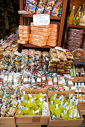 Small bottles ofr lemoncello and wine, backed by colorful bags of candy, pasta, and other local foodstuffs, draw shoppers to Enoteca La Cambusa on via Cavour in Stresa's pedestrians-only shopping heart.