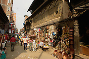 Two young girls walk arm in arm under an umbrella past copper pot merchants in busy street in Kathmandu's old town.