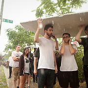 July 29, 2011 - Brooklyn, NY : From left to right, Matt Haveron, Eric Wiley and Mike Georup take shelter under a piece of styrafoam board they found at the roadside during a rain storm as they wait in line to enter the House of Vans at 25 Franklin Street in Greenpoint, Brooklyn on Friday night. Acts included the hardcore punk bands the 'Cro-Mags' and 'Fucked Up.' CREDIT: Karsten Moran for The New York Times