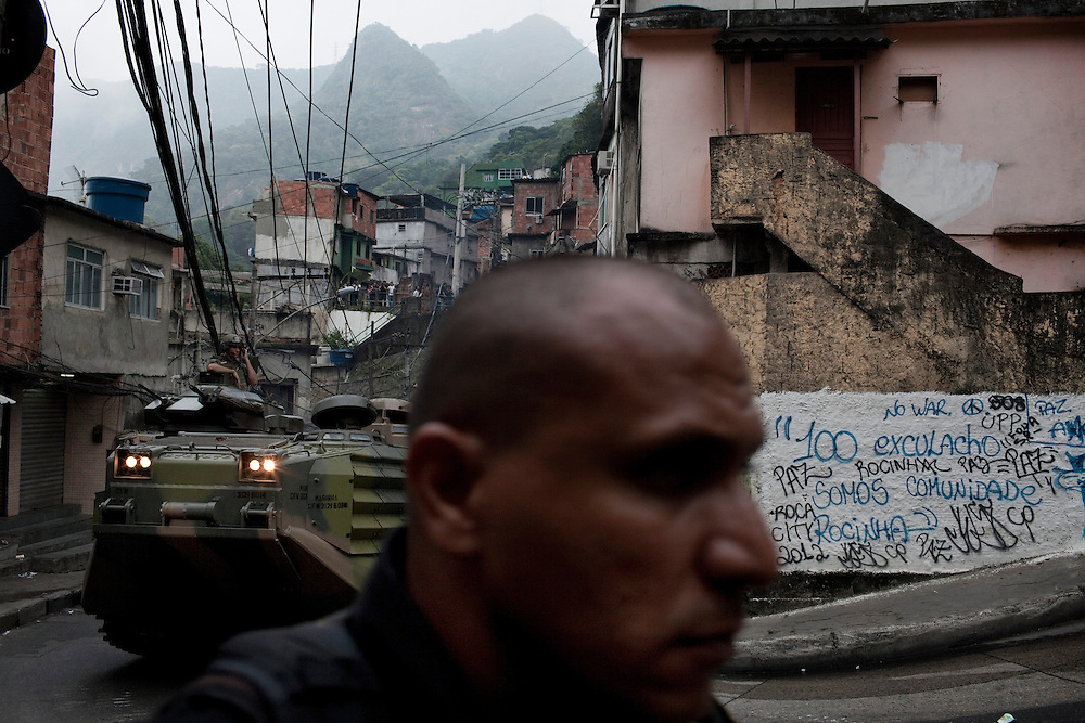 A policeman, member of BOPE special forces, move forward following an armored carrier of Brazilian Navy during an incursion by security forces into 'Rocinha', one of Brazil's biggest slums controlled by drug traffickers, on November 13, 2011, Rio de Janeiro, Brazil. Photo by Mauricio Lima for The New York Times
