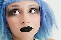 Close-up of young female punk with black lipstick, eye make-up and blue hair