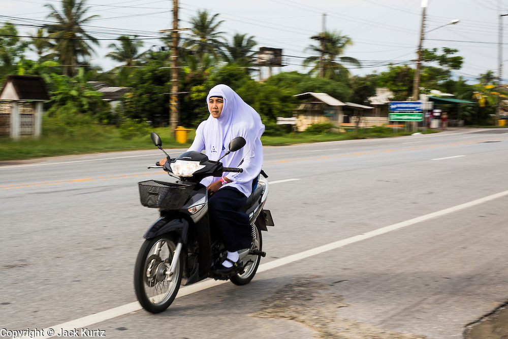 11 JULY 2013 - PATTANI, PATTANI, THAILAND:   A woman on a motor scooter goes by the Bantaladnadklongkud School in Pattani. There are 108 students at Bantaladnadklongkud School and they are all Muslims. Five of the school's eight teachers are Buddhists.    PHOTO BY JACK KURTZ