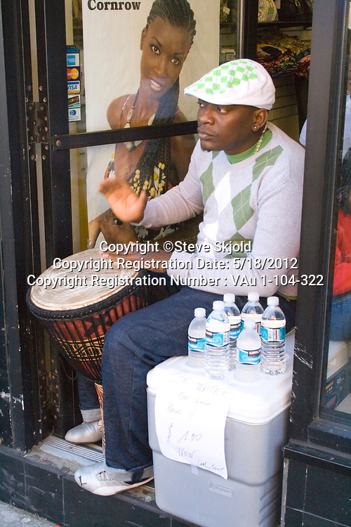 Handsome African American man playing conga drum in storefront. Mexican Independence Day Minneapolis Minnesota MN USA