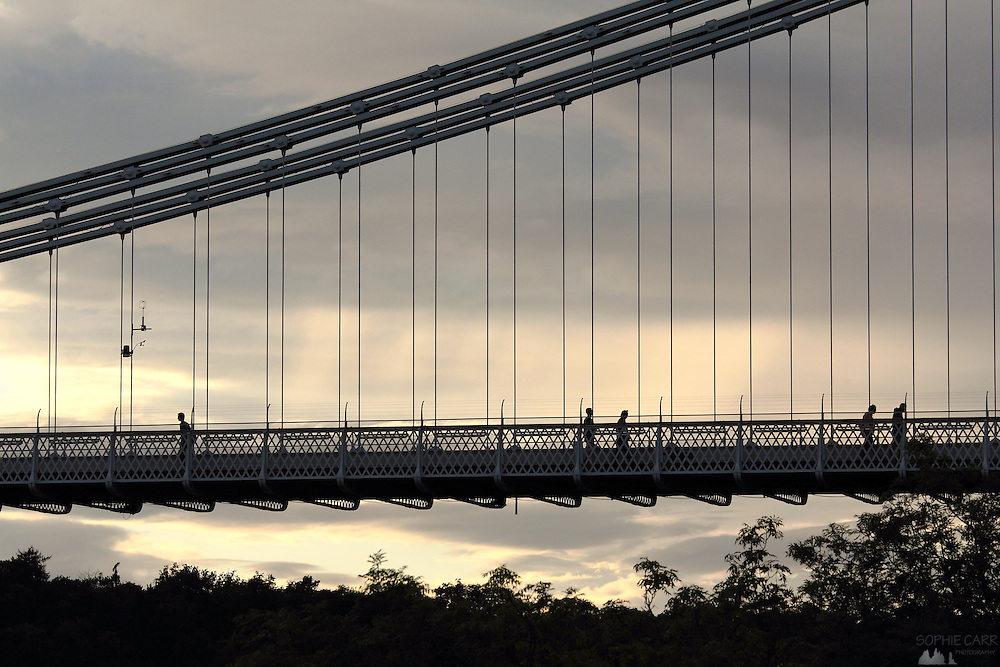 Silhouettes of people crossing the Clifton Suspension Bridge in Bristol