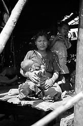 BANGLADESH UKHIA JUL94 - A woman from the Buddhist Chakma tribe feeds her infant child at her hut in the hills near Ukhia, south of Cox's Bazaar in southern Bangladesh...The Chakma tribe, also known as Changmas, are considered to be the largest tribe occupying the Chittagong Hill Tracts region of Bangladesh, as well as in India, where they have been settled for many generations. They have their own unique historical traditions, culture, folklore and language of Eastern Indo-Aryian origin, with the vast majority of Chakmas being followers of the Hinayana sect of Theravada Buddhism...jre/Photo by Jiri Rezac..© Jiri Rezac 1994