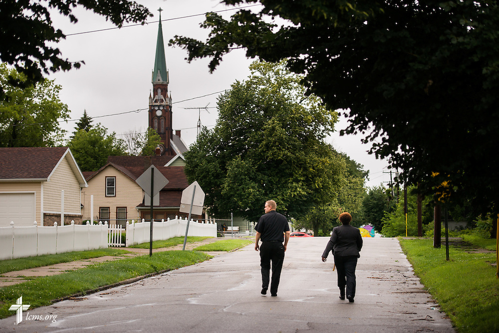 The Rev. Peter M. Burfeind, new domestic missionary and campus pastor at the University of Toledo, walks through a neighborhood with community advocate Alicia Smith on Thursday, July 9, 2015, in Toledo, Ohio. LCMS Communications/Erik M. Lunsford