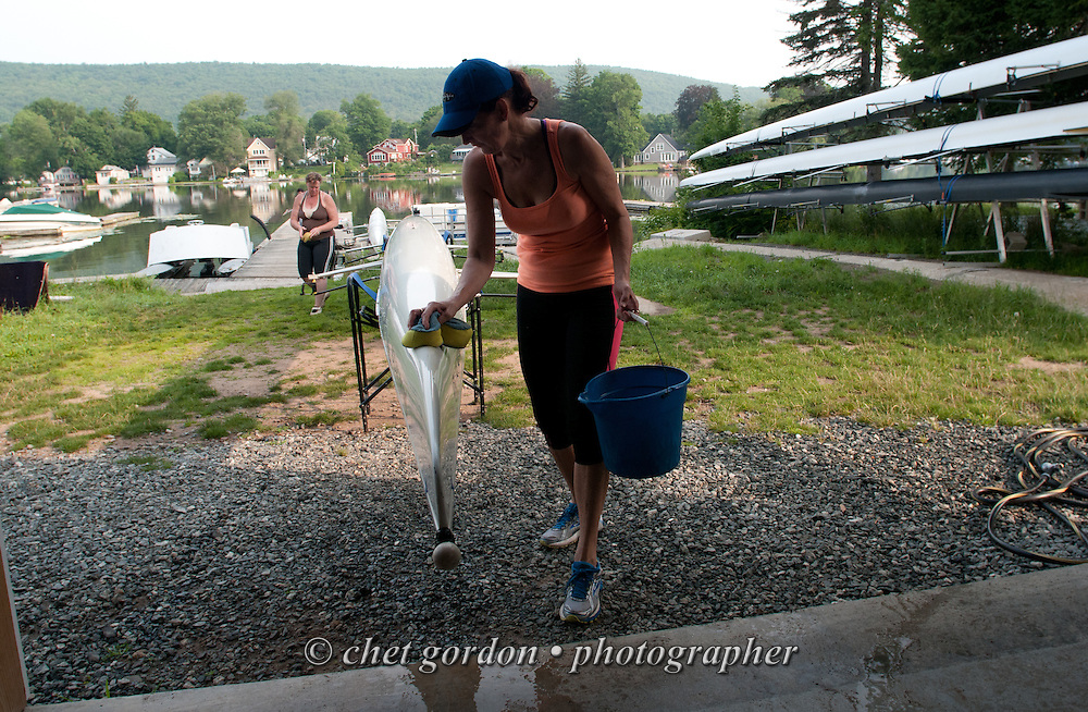 GREENWOOD LAKE, NY.  A women's crew team member cleans the hull of their boat after an early morning row at the East Arm Rowing Club in Greenwood Lake, NY on Monday, July 6, 2015.  © Chet Gordon/THE IMAGE WORKS