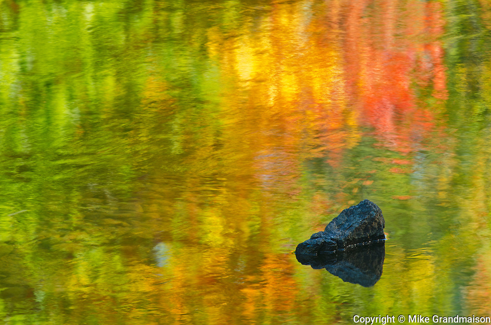 Rock and autumn reflections in Dryberry Creek. Sioux Narrows, Ontario