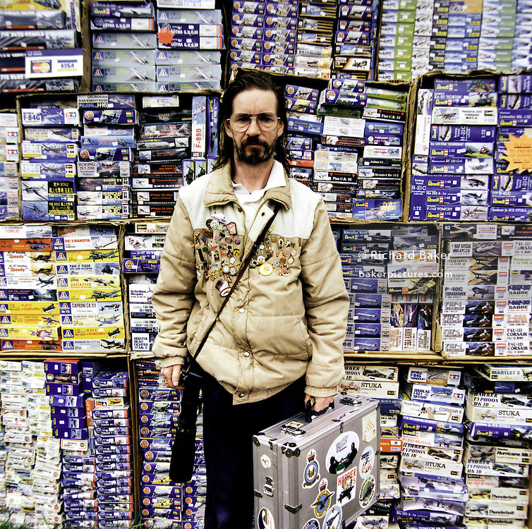 "A portrait of an aviation enthusiast with boxes of Airfix modelling kits during an airshow at North Weald in Essex, southern England. Holding a silver equipment case in one hand and his camera in another, the eccentric obsessive wears an anorak adorned with collectable badges and pins. Airfix is a UK manufacturer of plastic scale model kits of aircraft and other subjects. In Britain, the name Airfix is synonymous with the hobby, a plastic model of this type is often simply referred to as ""an airfix kit"" even if made by another manufacturer."