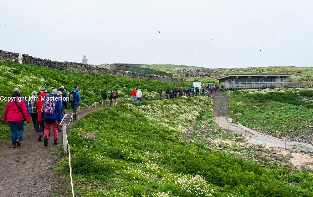 Birdwatchers walking towards Visitor Centre on Isle of May National Nature Reserve, Firth of Forth, Scotland, UK