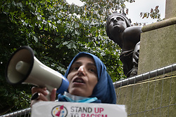 © Licensed to London News Pictures. 30/08/2020. Manchester, UK. A protester speaks in front of a statue dedicated to Robert Peel , in Piccadilly Gardens . The statue features two subsidiary allegorical female figures , one of which is pictured . Protesters and campaigners hold a combined Extinction Rebellion and Black Lives Matter protest in Manchester City Centre , during which statues and memorials are rededicated with new historical context highlighting the slave trade . Photo credit: Joel Goodman/LNP