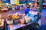 19 OCTOBER 2012 - BANGKOK, THAILAND:  A food vendor pushes her cart through the Bangkok Flower Market. Early in the day, the market takes over the streets in the area, after about 7AM the streets are fully reopened to traffic. The Bangkok Flower Market (Pak Klong Talad) is the biggest wholesale and retail fresh flower market in Bangkok.  The market is busiest between 3:30AM and 6AM. Thais grow and use a lot of flowers. Some, like marigolds and lotus, are used for religious purposes. Others are purely ornamental.        PHOTO BY JACK KURTZ