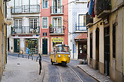 Piaggio Ape tuk tuk type three-wheeler passenger vehicle and tram tracks, narrow steep shopping street in Alfama District, Lisbon, Portugal