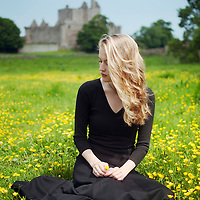Young woman with long blonde hair wearing a black dress sitting in field surrounded by buttercups