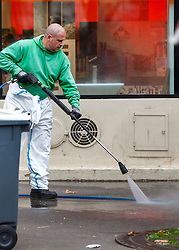 © Licensed to London News Pictures. 16/11/2015. Paris, France. Cleaners clean blood stains and remove personal items outside Bataclan Cafe in Paris, France following the Paris terror attacks on Monday, 16 November 2015. Photo credit: Tolga Akmen/LNP