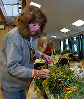 Cynthia McNutt puts together centerpieces with the Opechee Garden Club at the Weirs Community Center on Tuesday.  (Karen Bobotas/for the Laconia Daily Sun)