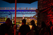 Picture by Andrew Tobin/Tobinators Ltd +44 7710 761829<br /> 04/08/2013<br /> Two riders taking part in the Alley Cat race cross a bridge whilst drinkers in a bar below look on during the Cycle Messenger World Championships held in Lausanne, Switzerland. Started in 1993 by Achim Beier from Berlin, the championships are not only a sporting contest but an opportunity to unite friends and bicycle enthusiasts worldwide. The event comprises a number of challenges including a sprint, a track stand (longest time stationary on the bike), a cargo race where heavy loads are carried on special bikes, and the main race. The course winds through central Lausanne and includes bridges, stairs, cobbles, narrow alleyways and challenging hills. The main race simulates the job of a bike courier making numerous drops and pickups across the city. Riders need to check in at specific checkpoints, hand over their delivery and get a new one. The main race can take up to 4 hours for each competitor to complete.