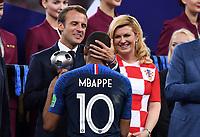 FUSSBALL  WM 2018  FINALE  ------- Frankreich - Kroatien    15.07.2018 Praesident Emmanuel Macron (li, Frankreich) und  Praesidentin Kolinda Grabar-Kitarovic (re, Kroatien) gratulieren Kylian Mbappe (Frankreich, Mitte) zur Auszeichung bester Jungspieler des Turniers.