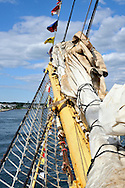 Bowsprit on sailing ship with furled sails, rope shroud and flags