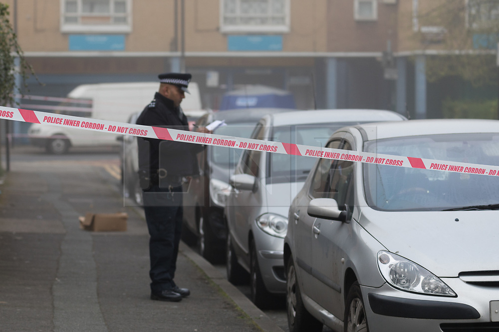 © Licensed to London News Pictures. 03/04/2017. LONDON, UK.  A police officer takes notes near the forensic tent at the crime scene and police cordon around BJ Wines in Freemasons Road, Canning Town, east London. Ahmed Jah, 21 is reported to have been knifed inside the off license, BJ Wines in Freemasons Road yesterday afternoon after he was set upon by a gang of men and stabbed in the chest. Emergency ambulance services attended and the man was pronounced dead at the scene shortly after.  Photo credit: Vickie Flores/LNP