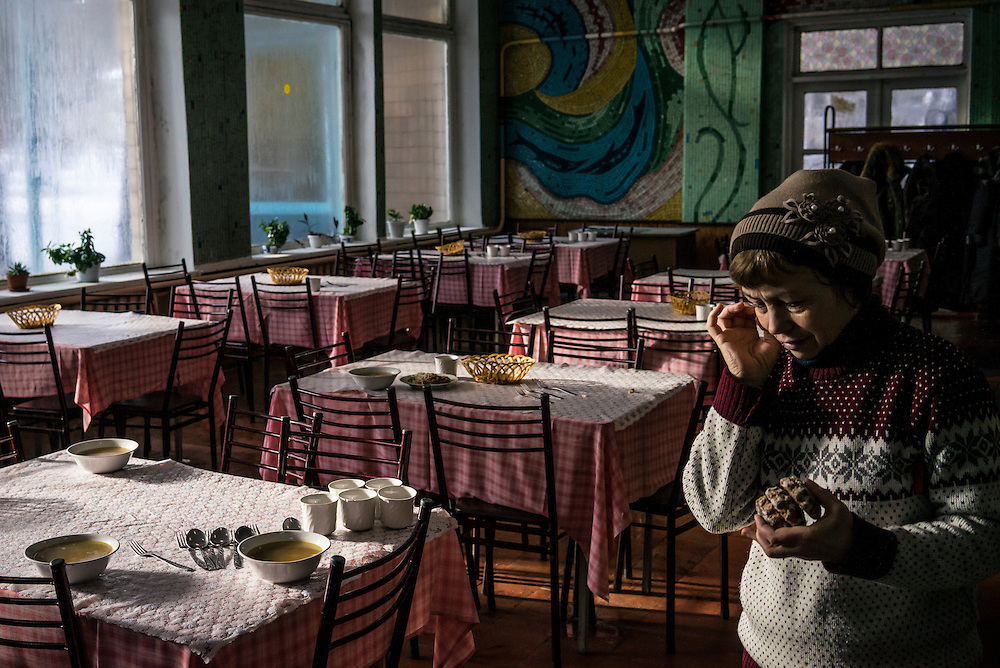 A woman who fled fighting between pro-Russia rebels and Ukrainian forces inside the canteen at the Perlyna Donetchyny children's resort, where she and several hundred others are temporarily seeking refuge, on Monday, February 9, 2015 in Svyatogorsk, Ukraine.