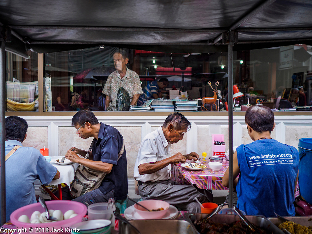 22 DECEMBER 2018 - CHANTABURI, THAILAND: Merchants in the gem market eat lunch from a street food cart in front of a gem cutting shop in Chantaburi. The gem market in Chantaburi, a provincial town in eastern Thailand, is open on weekends. Chantaburi used to be an active gem mining area in Thailand, but the mines are played out now. Now buyers and sellers come from around the world to Chantaburi for the weekend market. Many of the stones come from Myanmar, others come from mines in Afghanistan and Africa.      PHOTO BY JACK KURTZ