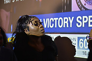 Garden City, New York, USA. November 6, 2018. Nassau County Democrats watch Election Day results at Garden City Hotel, Long Island. Woman wearing t-shirt with TAYLOR RAYNOR name on it had CNN news text and graphics - that were aimed at big screen behind her - projected on her face amd hair. Candidate Raynor won the NYS Assembly AD18 election.