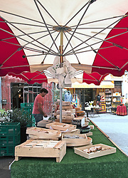 A cheese stall is ready for customers on a Sunday market day in L'Isle-sur-la-Sorge in Southern France's Luberon district.  A shopping hub for antiques, L'Isle-sur-la-Sorge is noted for its massive Sunday and Thursday markets as well as for the numerous decorator, furnishings, bric-a-brac, and vintage shops that draw visitors all days of the week.   The Sorgue River winds through the town's colorful streets and neighborhoods, a visual treat and the original source of the town's bustling economy.