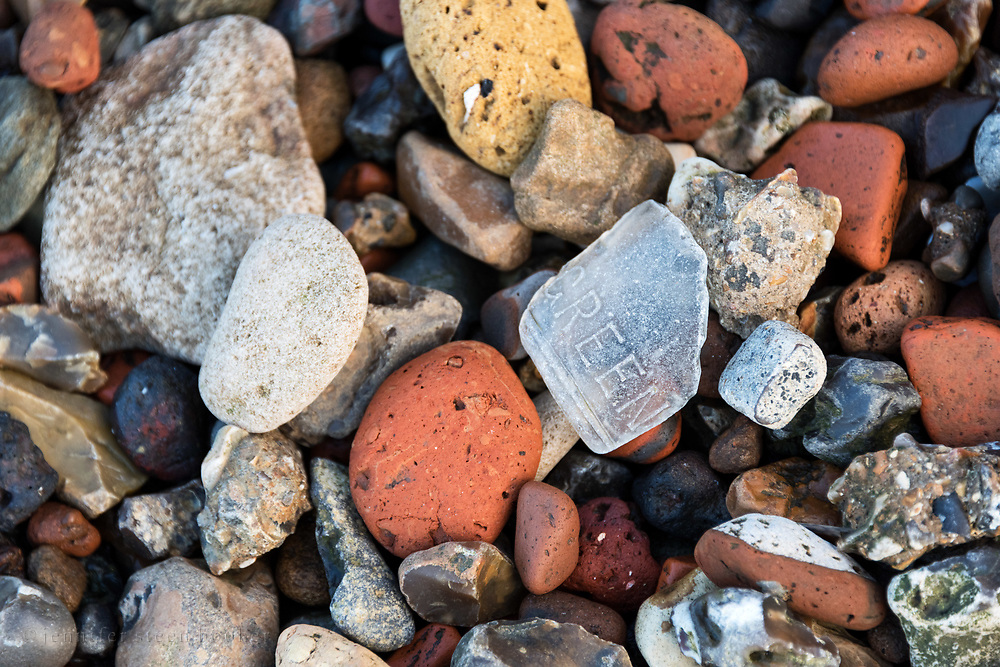 "Sea glass with the embossed word ""green"" among pieces of red and yellow brick, chalk, and flint on the Greenwich foreshore, London."