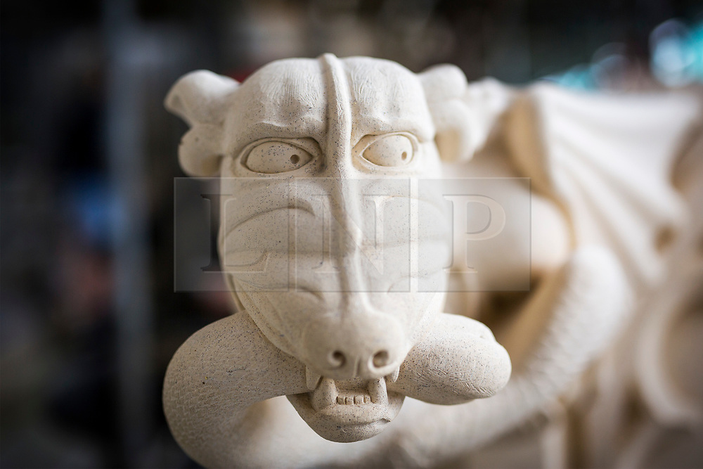 © Licensed to London News Pictures. 27/09/2017. York UK. The first collection of new grotesques to be carved for York Minster's 11 year project to conserve its South Quire Aisle have been installed today. The four carvings have been based on the Judgement of Solomon & include King Solomon, two women- one carrying a baby & a dragon holding a goose between it's teeth. The grotesques are being returned to a newly restored pinnacle, to replace four weathered carvings which are believed to date from the 1700s. Although badly eroded, the cathedral's stonemasons could make out two women - one holding a bundle – a male figure and evidence of a winged beast with a bird between its teeth. Work on the South Quire Aisle, which dates from the 14th century, began at the start of 2016 and will involve an £11m investment over the next decade to repair and replace stone and glass in 15 window bays.Photo credit: Andrew McCaren/LNP