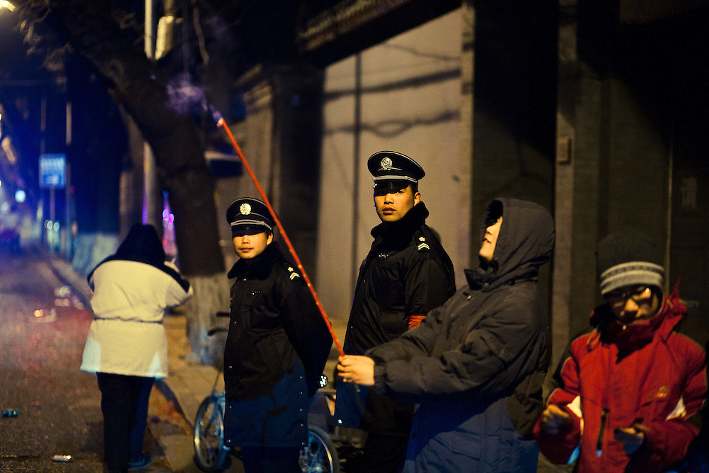Some chinese policemen are watching at beijingers who are lighting fireworks in a area close to the Tiananmen square, and the government buildings, while china is celebrating the New Year 2011 ( year of the rabbit) called Chunjie (spring festival). February 3 2011.