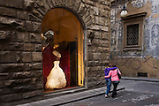 Young lovers pass an expensive wedding dress on display in the window of the bridal shop Atelier Aimee on Florence's Borgo degli Albizi street. Arm in arm the couple walk on by, unable to afford such an extravagant item of clothing for their future wedding day. Contemporary graffiti adorns the far wall below old frescoes that may be medieval but the only colour in this scene is from the lit shop window and dress and of the people.