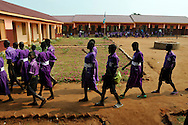 School children evacuate into a field behind their school while an Explosive Ordinance Disposal team from Mines Advisory Group (MAG) prepares to destroy a PM1 cluster sub munition found in the entrance of the school..Iriya, South Sudan. 01/07/2011..Photo © J.B. Russell