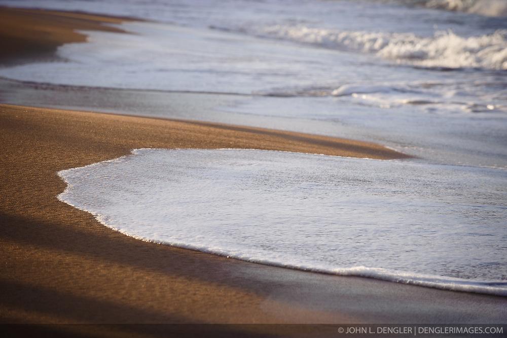Waves wash ashore onto beach sand on the shoreline of Wainiha Bay near the Hanalei Colony Resort on the north shore of the island of Kauai in Hawaii at sunset.