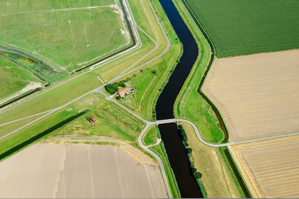 Nederland, Groningen, Oldambt,  05-08-2014; de Reiderwolderpolderdijk en boezemknaal van de Reiderwolderpolder uit 1870. De polder is ontstaan door landaanwinning, het inpolderen van kwelders van de Dollard.<br /> Reiderwolderpolder dike with bosom channel , Reiderwolderpolder from 1870. The polder is  created through land reclamation.<br /> luchtfoto (toeslag op standard tarieven);<br /> aerial photo (additional fee required);<br /> copyright foto/photo Siebe Swart