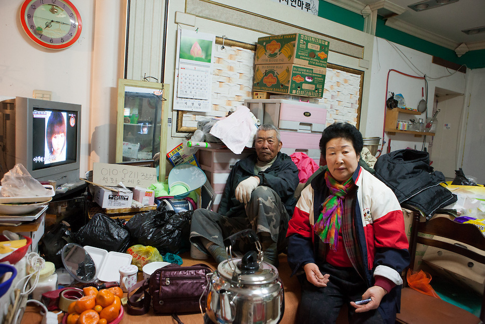 "Couple watching television in a vegetable and fruit shop in Jindo city (Jindo island). Jindo is the 3rd biggest island in South Korea located in the South-West end of the country and famous for the ""Mysterious Sea Route"" or ""Moses Miracle"" which is happening during full moon in spring."