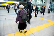 a small elderly gray haired woman walking by herself with a big backpack through a train station in Japan
