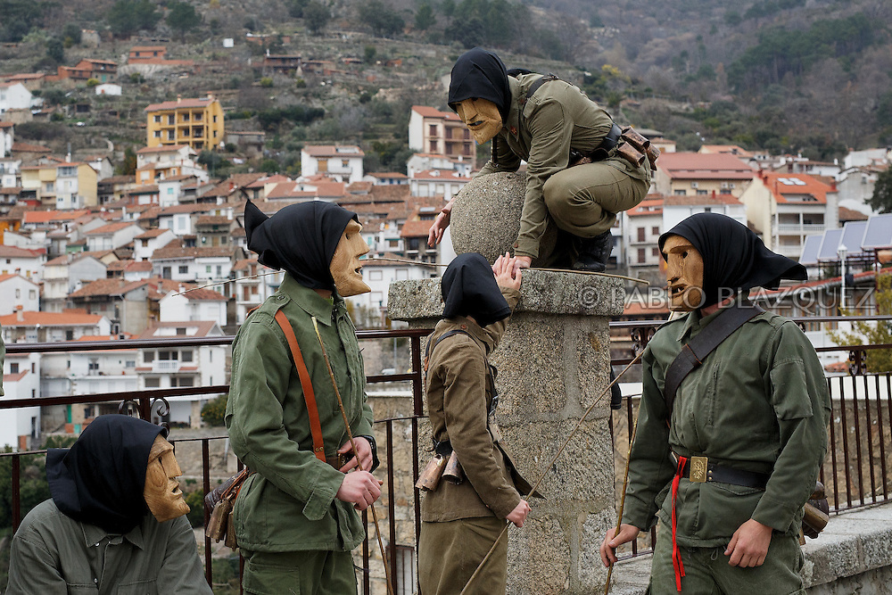 A Machurreros from Pedro Bernardo climbs down from a post in a park during Carnival on February 6, 2016 in Pedro Bernardo, in Avila province, Spain. The origins of this pagan festival are unknown. The Machurreros wear wood masks, a military dress, black handkerchief, cowbells, and hold wicker stick. The festival disappeared after Dictator Franco forbid carnival festivals in 1937, but it was recently recovered. Before disappearing, male villagers after the military service, used to dress as Machurreros as they run along the streets scaring children and adults with their wicker stick to bring fertility to the land and expel the evil spirits. (© Pablo Blazquez)