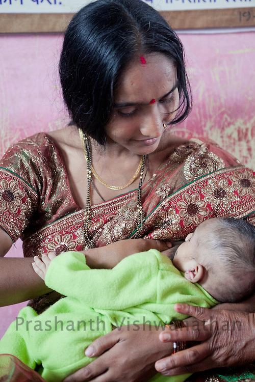Dolasane. Sangamner Block, Ahmednagar, Maharashtra, India, 23 years old Lalita Kshirsagar breast feeds her one and a half month old son, at the anganwadi center, in Dolsane.   July 2012:.UNICEF India/2012/Vishwanathan.  UNICEF India/2012/Vishwanathan