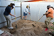 The Green Living Co-op volunteers get right to work. They're spreading the sand that will serve as a base for my cistern.