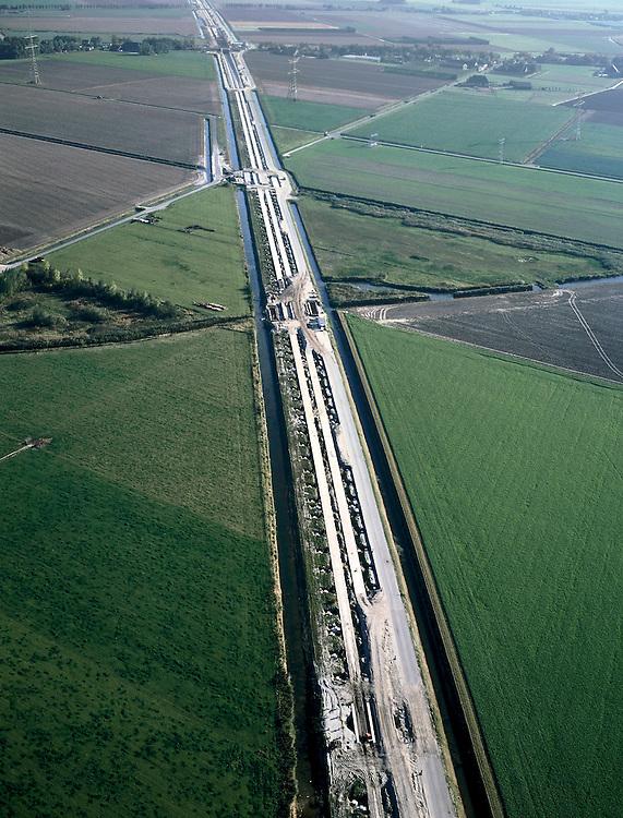 Nederland, Zuid-Holland, Hoeksche Waard, 17-10-2003; aanleg HSL, de hogesnelheidslijn doorsnijdt het polderlandschap diagonaal (richting Brabant); links en rechts van de nieuwe spoorbaan de spoorsloten, de baan zelf zal uit een zogenaamde zettingsvrije plaat bestaan: deze plaat is gefundeerd op heipalen, de spoorstaven worden direkt op deze plaat aangebracht (dus zonder dwarsliggers (bielzen) in ballastbed); verkeer en vervoer, transport, infrastructuur, bouwen, spoor, rail, planologie ruimtelijke ordening, landschap;<br /> luchtfoto (toeslag), aerial photo (additional fee)<br /> foto /photo Siebe Swart