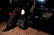 A girl in high heeled boots, with a handbag, getting out of a car, Girlracers, Southend, UK 2004