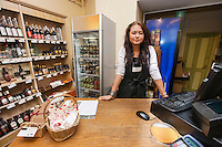 Portrait of young saleswoman standing at cash counter in supermarket