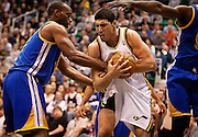 Jazz center Enes Kanter (0) rips away the ball from Warriors forward Carl Landry (7), left, during the first half of the NBA basketball game between the Utah Jazz and the Golden State Warriors at Energy Solutions Arena, Wednesday, Dec. 26, 2012. The foul prompted a tussle between players resulting in multiple technical fouls.